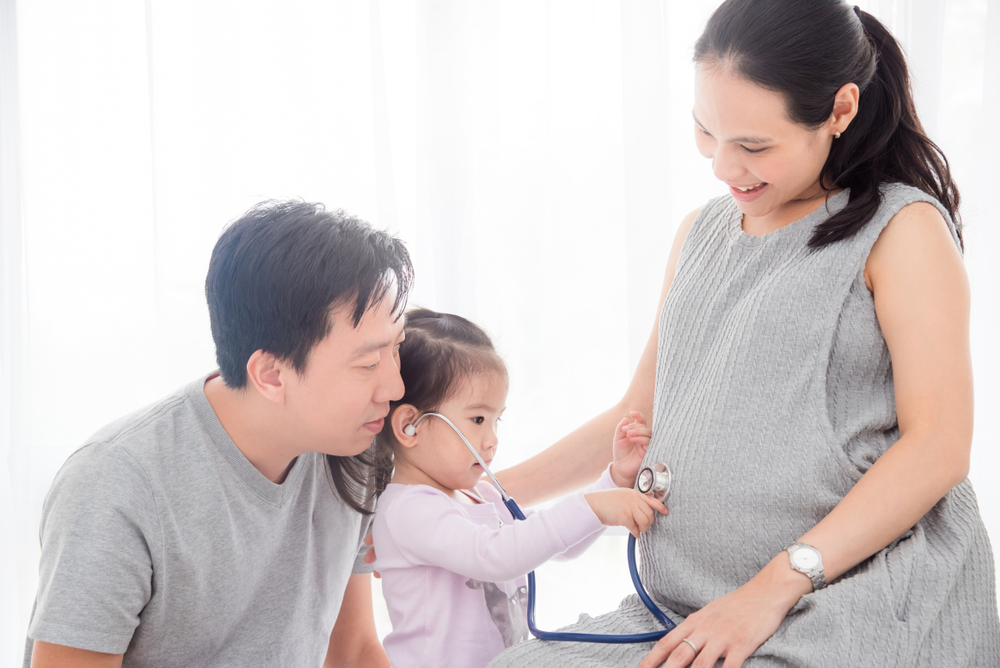 Pregnant woman and her child play with a stethoscope at home.
