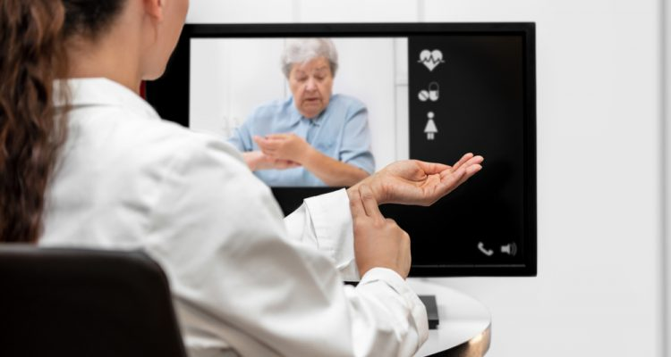 Doctor and senior woman taking pulse together via remote care